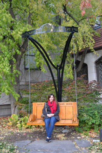 Daniela lounging on a beautifully-carved wooden swing